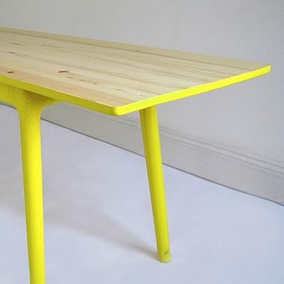 Drewniany stolik z żółtymi nogami i spodem