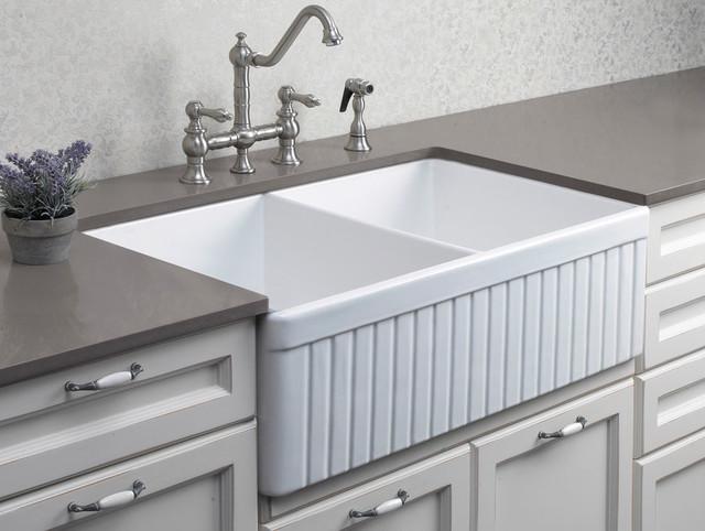 dwukomorowy zlew ceramiczny, biały, z głębokim dnem. Obok kranu znajduje się wbudowany w szafkę dozownik płynu