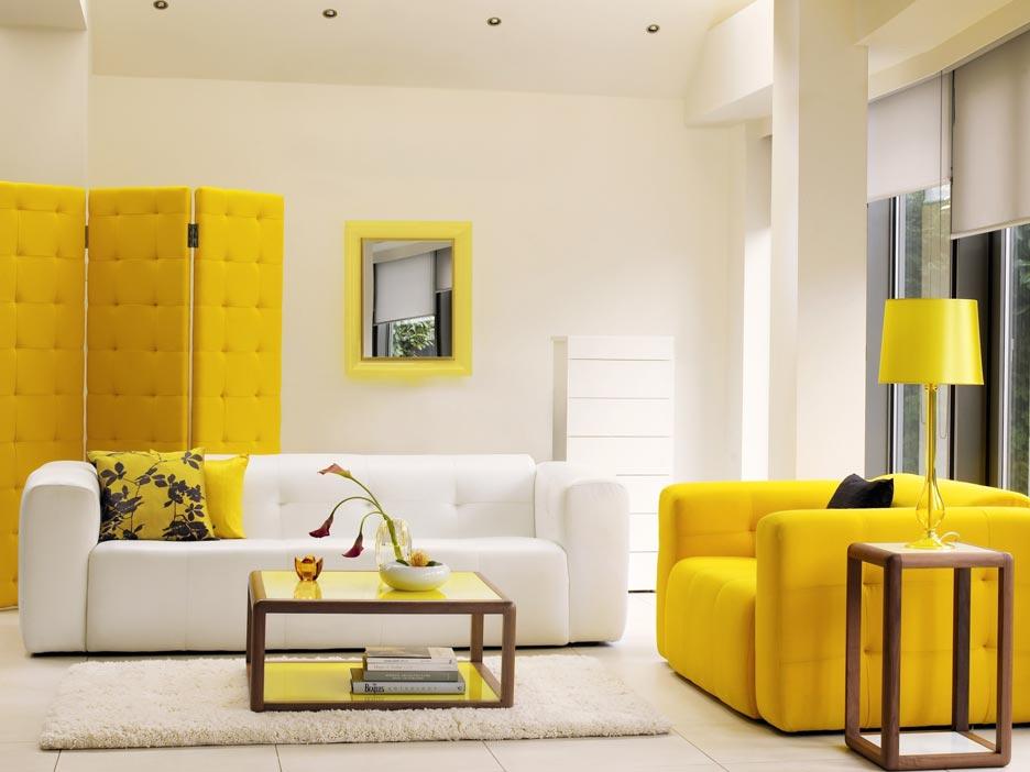 Salon w bieli z mocnym akcentem żółci w postaci kanapy, parawanu i lampy