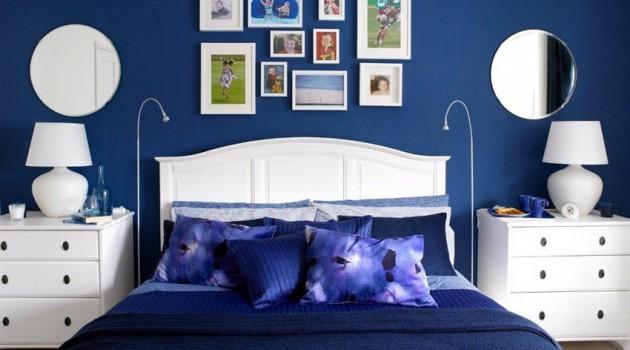 Sypialnia z białymi meblami i granatowymi ścianami oraz dodatkami