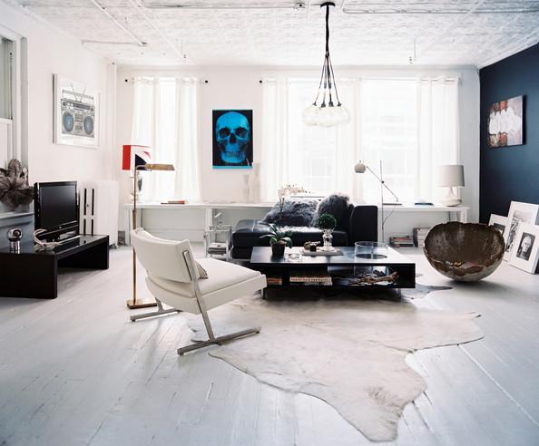 Minimalistyczny salon z dekoracjami naturalnymi w odcieniach czerni i bieli. Nad stołem zamiast lampy wiszą duże, okrągłe żarówki