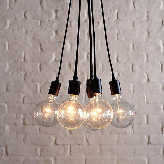 Lampa złożona z żarówek na kablach, na tle bielonej, ceglanej ściany