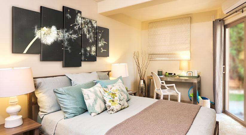Sypialnia z kolażem nad zagłówkiem łóżka, przedstawiającym mniszka lekarskiego