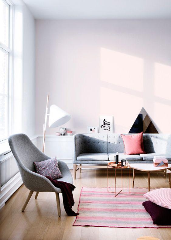 Jasny, minimalistyczny salon urządzony w szarościach, z delikatnym różem na ścianach i dodatkami w różnych odcieniach różu