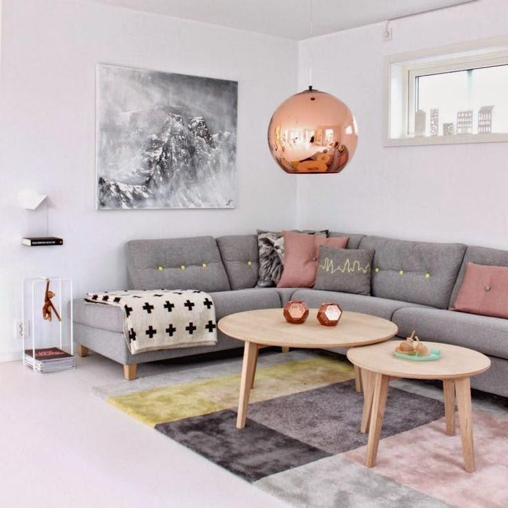 Nowoczesny, minimalistyczny salon urządzony w szarościach, z dodatkami w kolorze przybrudzonego różu w postaci poduszek dekoracyjnych