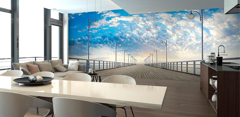 Mały salon z aneksem kuchennym z dużą, realistyczną fototapetą, przedstawiającą molo - sprawia wrażenie, że pokój jest o wiele większy