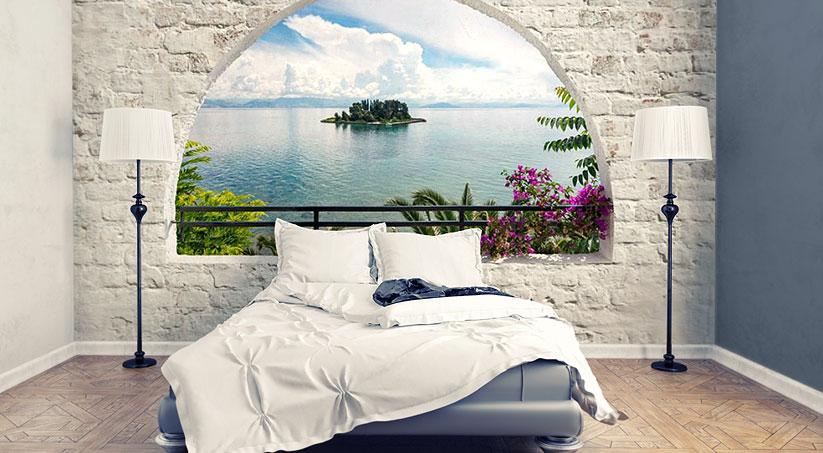 Sypialnia w śródziemnomorskim stylu: nad łóżkiem znajduje się fototapeta imitująca okno z widokiem na morze. Powieszona jest na ścianie wyłożonej kamieniem bielonym