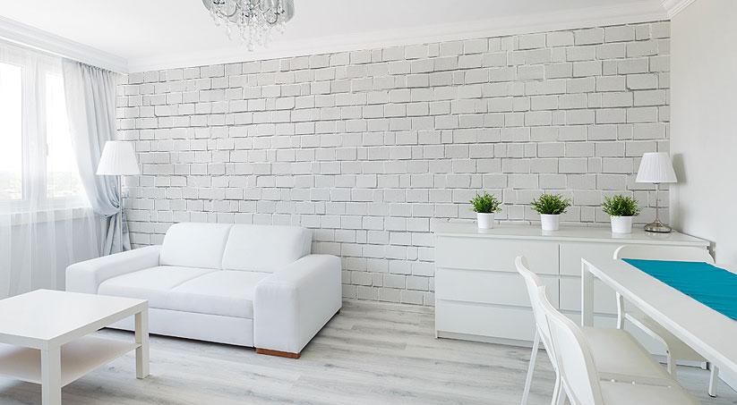 Minimalistyczny salon, utrzymany w skandynawskim klimacie, z fototapetą imitującą kamienną, bieloną ścianę