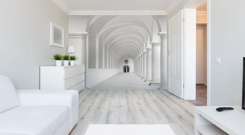 Mały salon zaaranżowany w bieli - węższa ściana wyłożona jest fototapetą przedstawiającą długi korytarz - pomieszczenie wydaje się o wiele większe