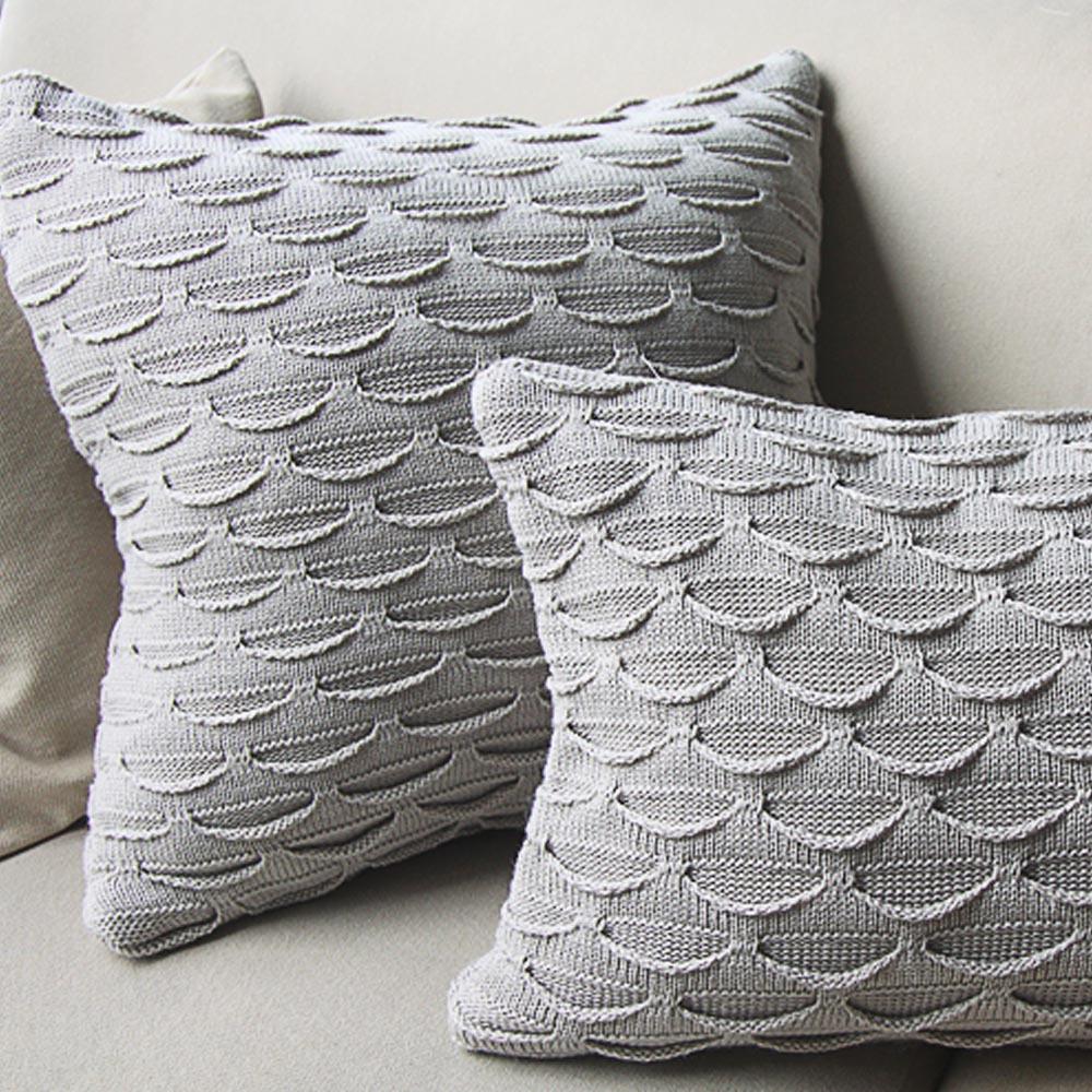 Szare poduszki dekoracyjne z poszewkami wykonanymi na drutach, o nietypowym wzorze w kształcie łódek