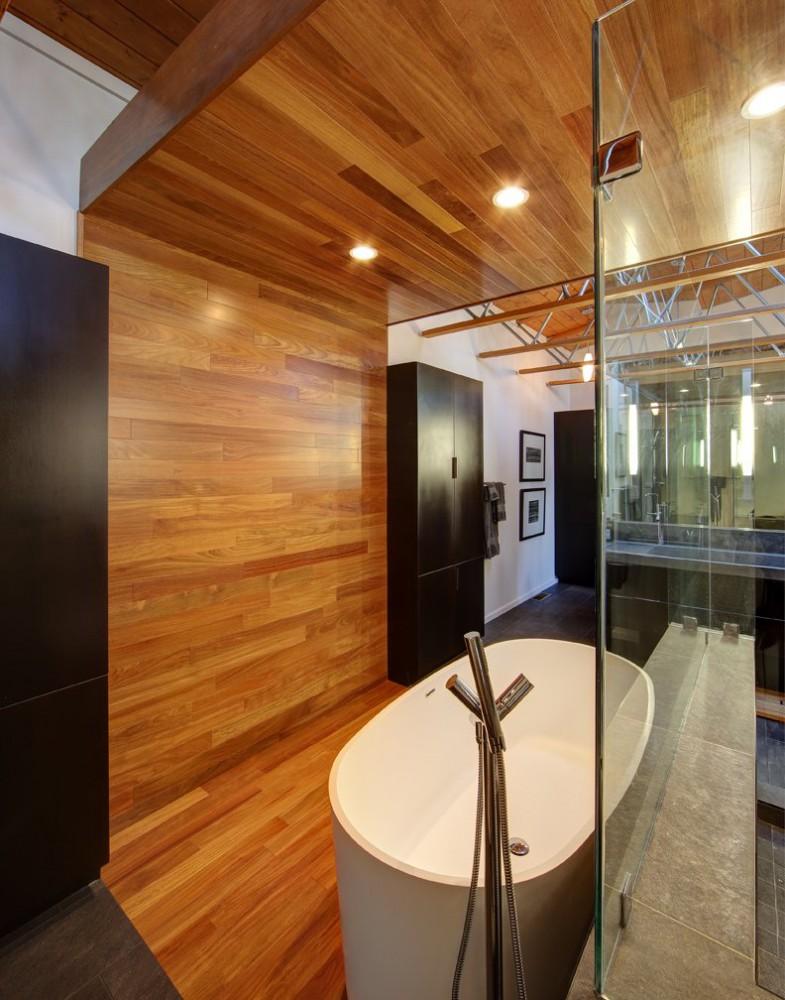 Nowoczesna łazienka łącząca przeszklenia z drewnem na podłodze, ścianie i suficie