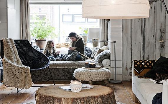 Salon w stylu skandynawskim, z dodatkami robionymi na drutach, w postaci pufy i pledu