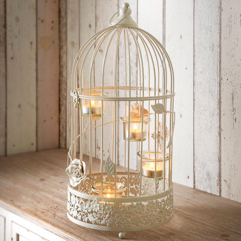 Biała latarnia imitująca klatkę dla ptaka, ze świeczkami na różnej wysokości
