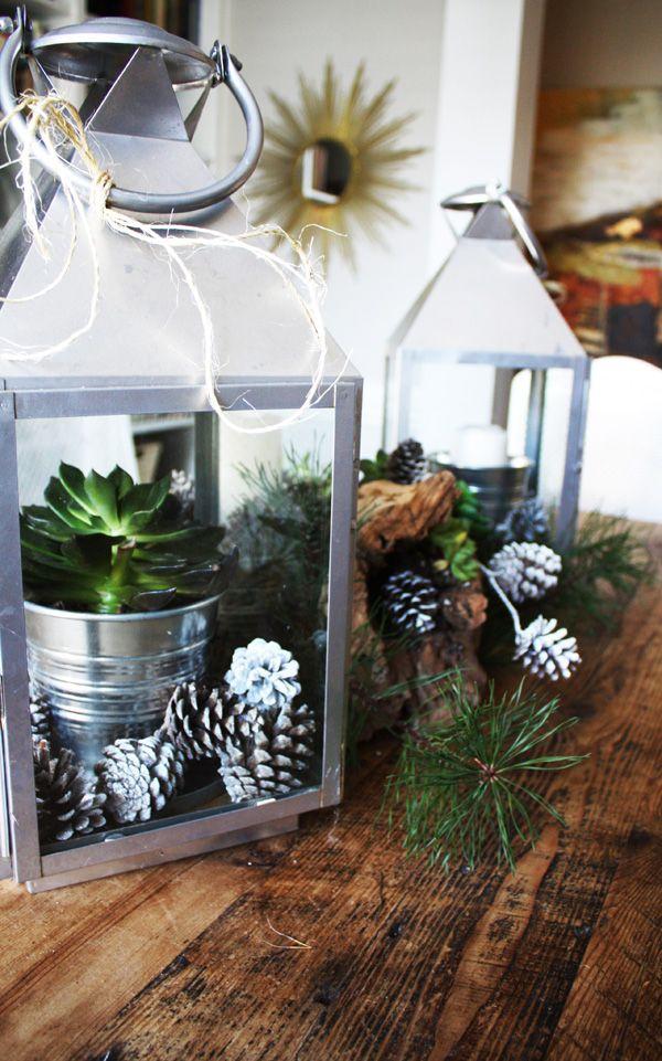 2 białe latarnie, z metalowymi elementami, szyszkami i roślinami