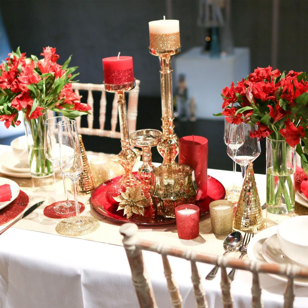 Prosty stroik ze szklanych świeczników, świec, małych dekoracji i talerza