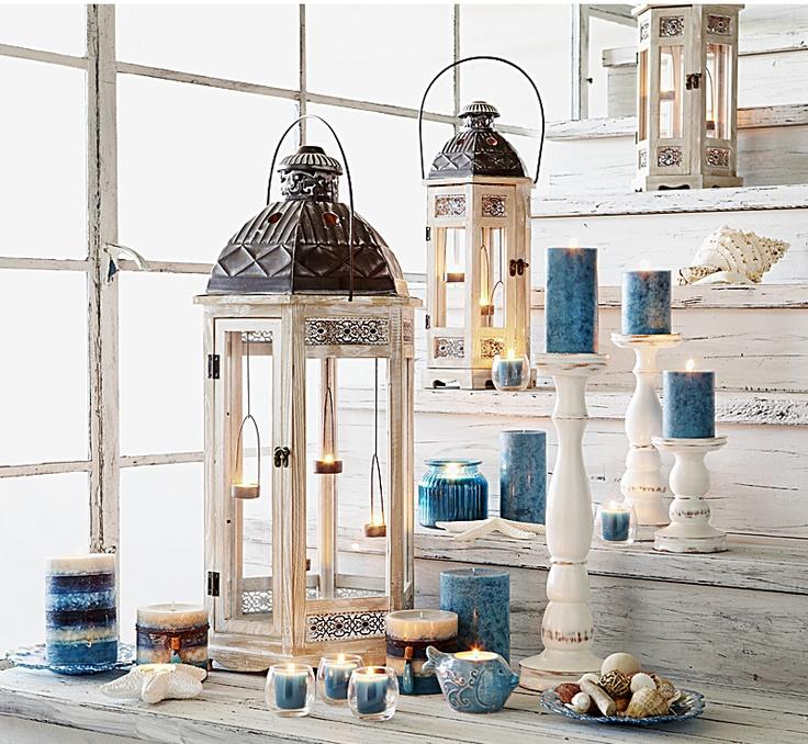 3 latarnie w stylu skandynawskim w otoczeniu świec w kolorach niebieskich, szarych i białych