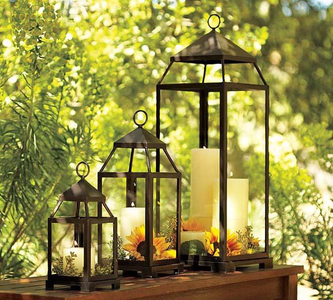 3 brązowe latarnie różnej wysokości ozdobione naturalnymi dekoracjami - słoneczniki, liście, gałązki