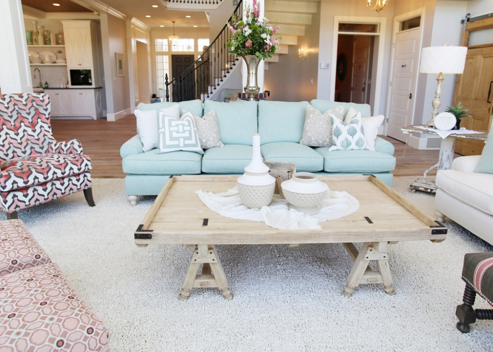Elegancki, jasny salon z delikatnymi akcentami różowego kwarcu i niebiańskiego spokoju,w postaci poduszek, kolorystyki dywanu i kanapy
