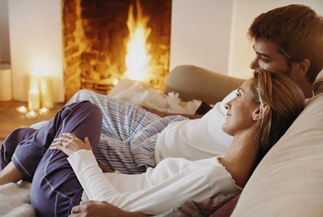 Para spędzająca wieczór przy kominku w domu