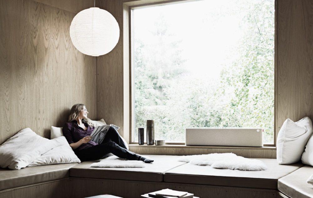 Kobieta siedząca na siedzisku obok okna