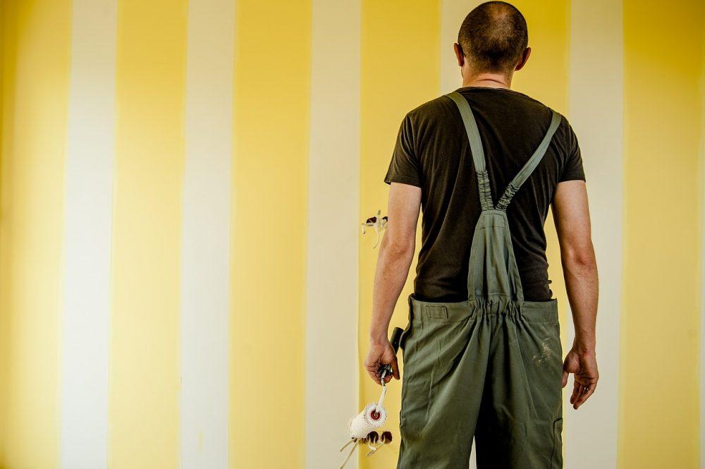 Mężczyzna z wałkiem w ręku malujący ścianę w pasy
