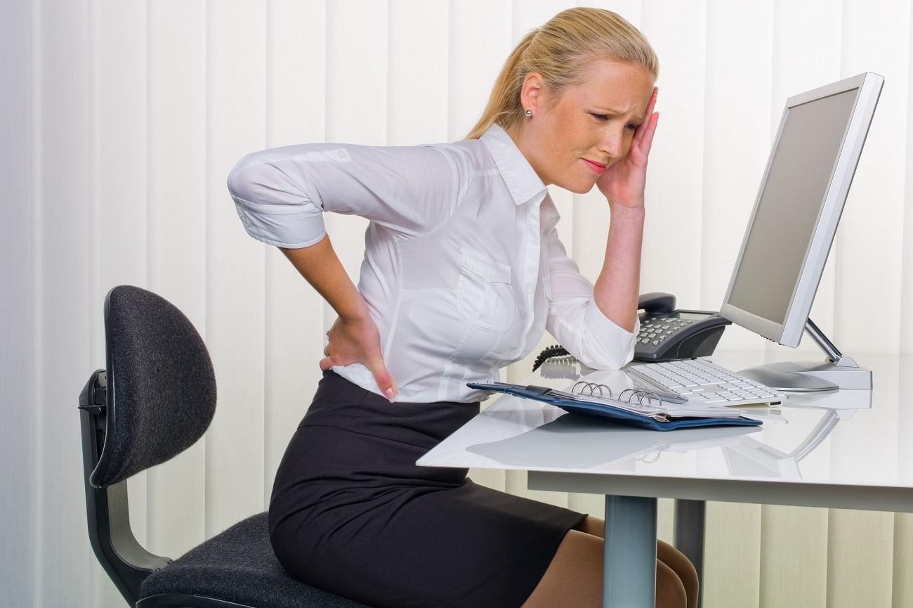 Kobieta za biurkiem z bólem kręgosłupa