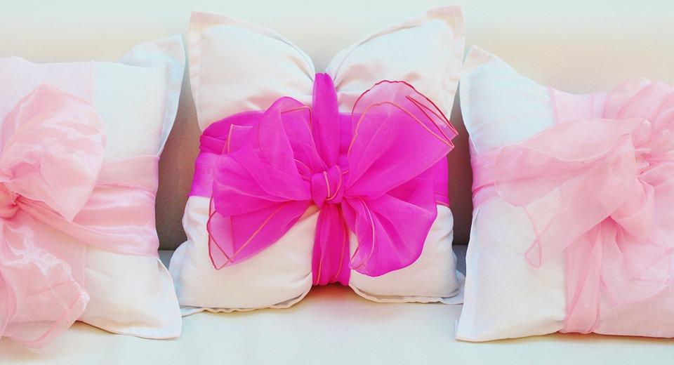 Poduszki przewiązane różowymi, tiulowymi kokardami