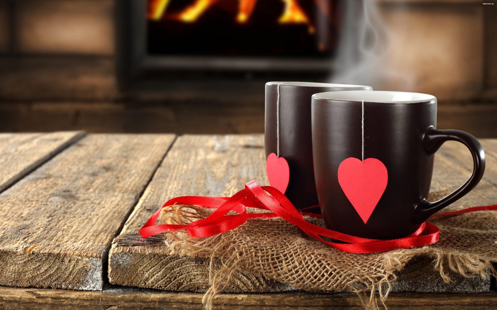 Dwa kubki z herbatą, a w tle kominek