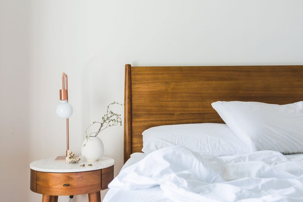 Łóżko drewniane i okrągły stolik nocny