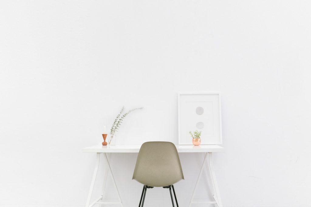 Białe wnętrza - stolik i krzesło na tle białej ściany