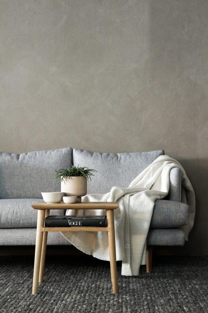 Delikatne tynki strukturalne, jasna sofa i drewniany stolik