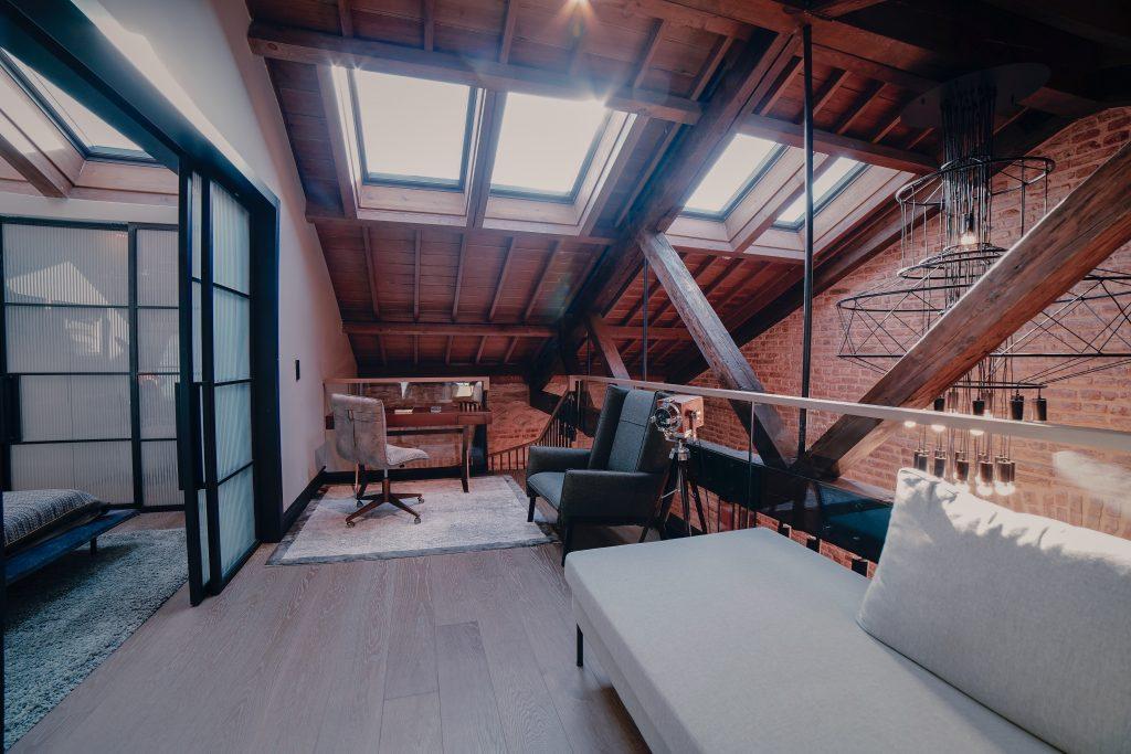 Aranżacja poddasza - wyeksponowana więźba dachowa i ekskluzywne meble