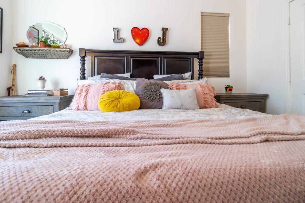 Łóżko i dwie różne szafki nocne - aranżacja sypialni