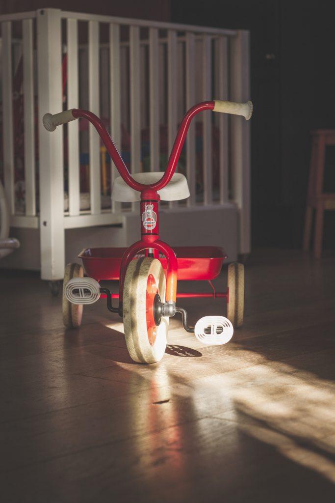 Детский велосипед на деревянном полу - детская комната