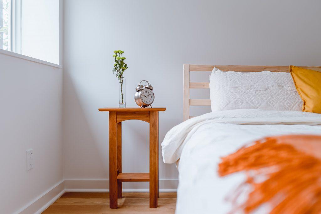 Drewniany stolik nocny koło łózka